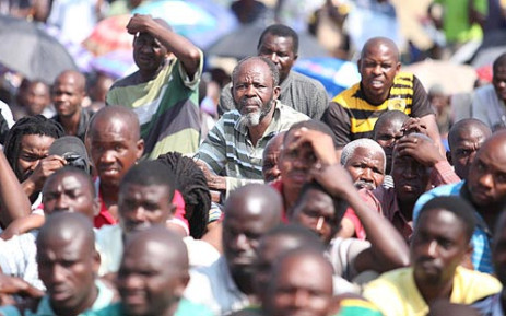Striking Lonmin workers discuss a wage increase offer in Marikana, North West, on 14 September 2012. Picture: Taurai Maduna/EWN.