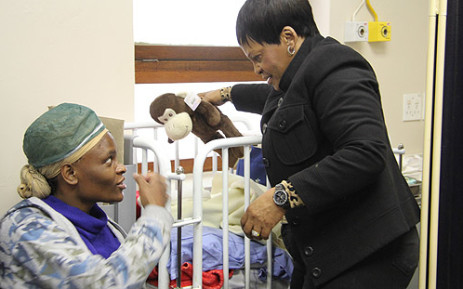"Gauteng Premier Nomvula Mokonyane speaks to a mother on Mandela Day at Chris Hani Baragwanath in Soweto. Picture: Taurai Maduna/EWN"""