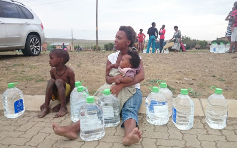 A mother sits on the pavement with her children after collecting water from the Operation Hydrate team in Steynsrus, Free State on 23 January 2016. Picture: Abed Ahmed/EWN.