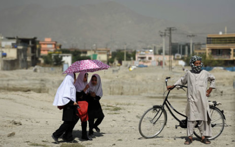 Passing Afghans watch a demostration against Pakistan intervention in Afghanistan, in Kabul on August 30, 2012. The demonstrators demanded that the United Nations (UN) stop Pakistan military and political intervention in the country. Picture: AFP.
