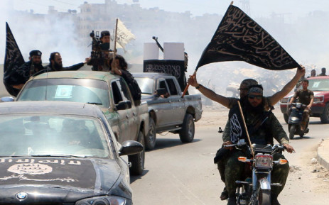 Fighters from Al-Qaeda's Syrian affiliate Al-Nusra Front drive in the northern Syrian city of Aleppo flying Islamist flags as they head to a frontline, on 26 May 26 2015. Picture: AFP/AMC/Fadi Al-Halabi.