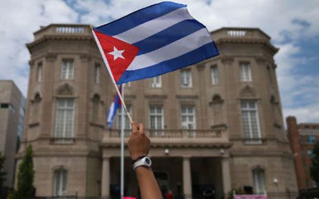 FILE: A supporter waves a Cuban flag in front of the country's embassy after it re-opened for the first time in 54 years 20 July, 2015 in Washington, DC. Picture: AFP.