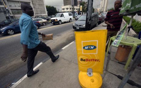 FILE. A man walks past a MTN notice board in Lagos, on 27 October 2015. Nigeria's telecommunications regulator has fined South African mobile giant MTN $5.2 billion for missing a deadline to disconnect unregistered SIM cards. Picture: AFP