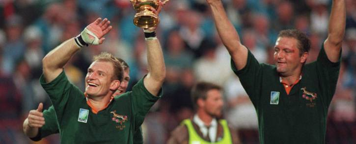 South African captain Francois Pienaar (left) brandishes the Rugby World Cup and salutes the crowd with teammate Hannes Strydom (right) after the 1995 Rugby World Cup final match South Africa vs New Zealand at Ellis Park Stadium in Johannesburg on June 24, 1995. Picture: AFP.