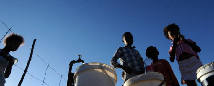 Youths fill their buckets with water from a tap after water supply was restored in Boitumelong Township in Bloemhof, North West on 29 May 2014. Picture: Sapa.