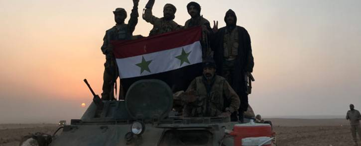 FILE: Syrian forces gestures as they carry the national flag in the village of Suway'iah, near the Syrian border town of Albu Kamal, on 9 November 2017. Picture: AFP