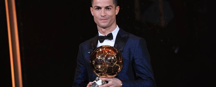 This handout photo released on 7 December, 2017 by L'Equipe shows Portugese player Cristiano Ronaldo posing with the Ballon d'Or France Football trophy in Paris. Picture: AFP.