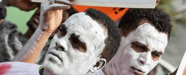 FILE: African migrants demonstrate with white paint on their faces, outside the Embassy of Rwanda in the Israeli city of Herzliya on 7 February 2018. Picture: AFP