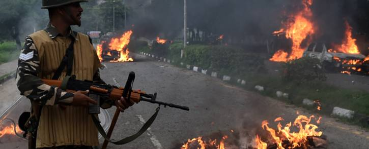 Indian security personnel looks at burning vehicles set alight by rioting followers of a religious leader convicted of rape in Panchkula on 25 August, 2017. Picture: AFP.