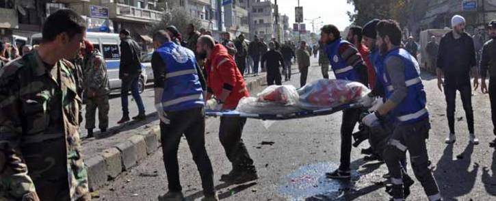 Emergency services remove a body from the site of a car bomb explosion in a predominantly pro-government neighbourhood of the central Syrian city of Homs on 5 December 2107. Picture: AFP.