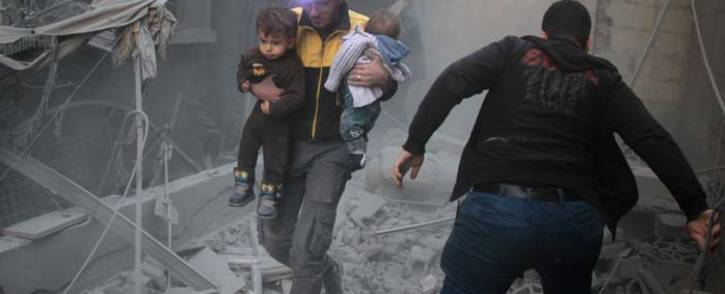 FILE: A Syrian man carries two children in the rubble of buildings following regime air strikes on the rebel-held besieged town of Douma in the eastern Ghouta region. Picture: AFP.