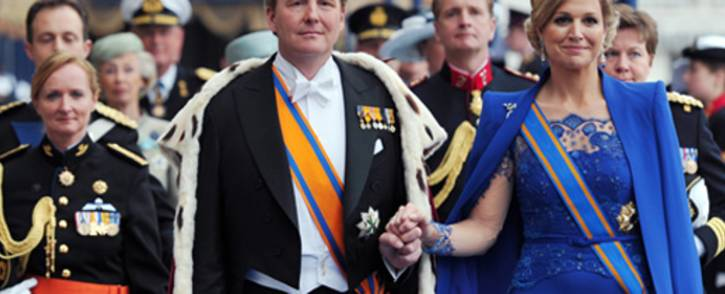 FILE: King Willem-Alexander of the Netherlands leaves with his wife Queen Maxima the Nieuwe Kerk in Amsterdam on April 30, 2013 following his investiture. Picture: AFP