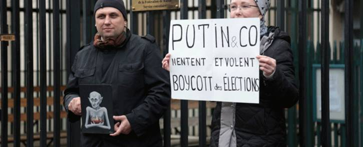 FILE: Protesters hold a caricature showing Russian President Vladimir Putin (L) and a placard reading 'Putin&Co lie and steal - boycott the elections' in front of the Russian Embassy in Paris on 28 January 2018, during a rally called for by Russian political activists in support of Russian opposition leader Alexei Navalny. Picture: AFP.