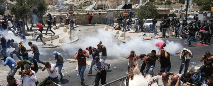 FILE: Palestinian worshippers run for cover from teargas fired by Israeli forces outside Jerusalem's Old City in front of the Al-Aqsa mosque compound on 21 July 2017. Picture: AFP.
