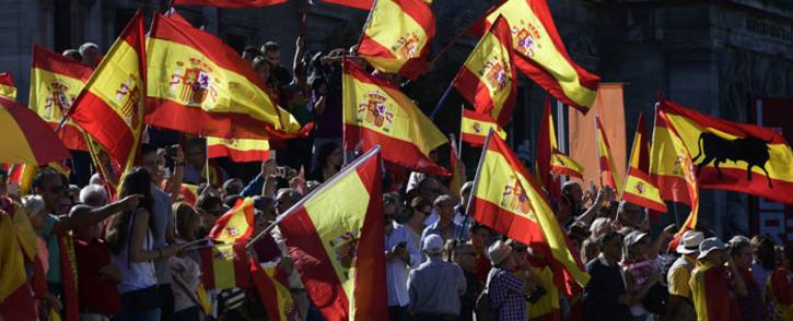 FILE: Protestors gather holding Spanish flags during a demonstration against independence of Catalonia called by DENAES foundation for the Spanish Nation Defence at Colon square in Madrid on 7 October 2017. Picture: AFP.