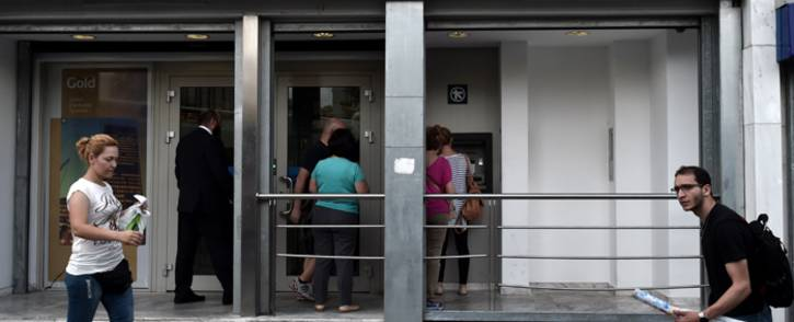People withdraw cash from ATMs in central Athens on 19 June, 2015, as a beggar lays on the pavement. The European Central Banks decision-making governing council will hold an emergency session on June 19 to discuss a request from the Bank of Greece for an increase in liquidity to Greek banks. Picture: AFP.