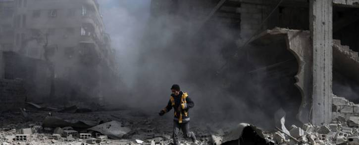 A civil defense volunteer, known as the White Helmets, checks the site of a regime air strike in the rebel-held town of Saqba, in the besieged Eastern Ghouta region on the outskirts of the capital Damascus, on 23 February 2018. Picture: AFP