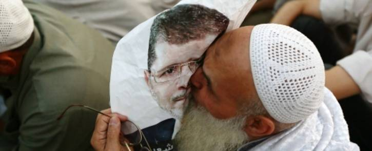 FILE: An Egyptian man, supporter of the Muslim Brotherhoo, kisses a poster of Mohamed Morsi as worshipers gather for prayer outside Cairo's Rabaa al-Adawiya mosque in 2013. Picture: AFP.