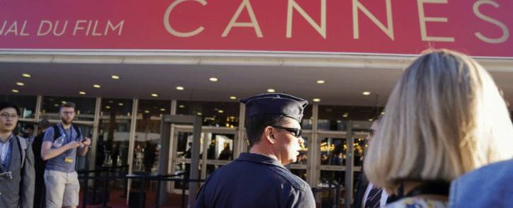 A Police officers stands guard as people wait outside the main entrance of the Festival's Palace on 20 May 2017 after it was evacuated over a suspicious package, at the 70th edition of the Cannes Film Festival in Cannes, southern France. Picture: AFP.