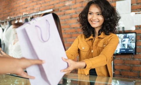 smiling-assistant-hands-over-shopping-bag-in-storejpg