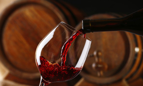 Pouring red wine from bottle into glass with wooden wine casks winemaking 123rf