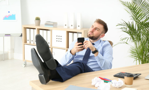 Procrastination procrastinator lazy office worker wasting time on phone 123rf