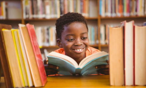 Little boy reading in library books 123rf