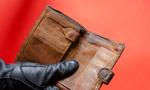 gloved-hand-holds-out-empty-wallet-fraud-theftjpg