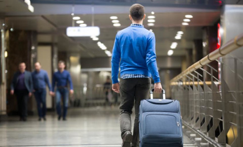 Young man pulling suitcase in modern airport terminal 123rf