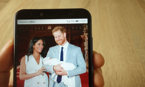 Prince Harry and Meghan Markle with baby on cell phone