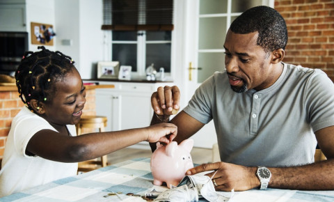 dad-and-daughter-saving-money-in-piggy-bankjpg