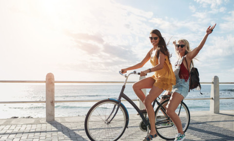 Young happy attractive women females riding bicycle Sea Point Promenade 123rf
