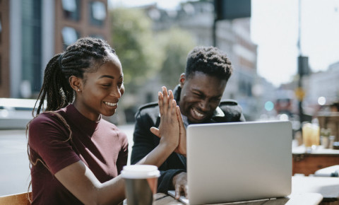 Young couple high-five looking at laptop screen 123rf