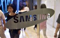 People walk past the logo of Samsung Electronics at the company's headquarters in Seoul on 30 July 2015. Picture: AFP/Jung Yeon-Je.