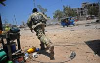 FILE: A Somali soldier runs for cover at the scene of two explosions set off near the ministries of public works and labour in Mogadishu on 23 March 2019. Picture: AFP