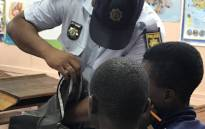A SAPS officer searches a learner's bag during a search and seizure operation at Woodlands Secondary School in Mitchells Plain, Cape Town. Picture: Kaylynn Palm/EWN
