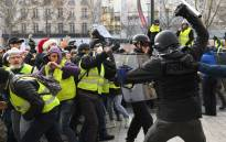 "FILE: Riot police clash with men wearing ""yellow vests"" (gilets jaunes) protestors on 8 December 2018 near the Arc de Triomphe in Paris during a protest against rising costs of living they blame on high taxes. Picture: AFP"