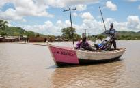 People and their goods are moved across the floodplains in Phaloni using traditional wooden fishing boats. Picture: Aletta Gardner/EWN