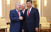 FILE: US Ambassador Terry Edward Branstad (L) shakes hands with Chinese President Xi Jinping (R) at the Great Hall of the People in Beijing on 30 September 2017. Picture: AFP