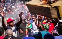 Fees2017 protesters fling a burning mock coffin into police barricade during the protesters march to parliament on the 26th October 2016. Picture: Anthony Molyneaux/EWN