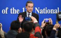 "China's Foreign Minister Wang Yi waves to journalists as he arrives for a National People's Congress press conference in Beijing on 8 March 2019. China threw its weight behind Huawei's legal battle against the United States on 8 March, vowing to take all necessary measures to defend the ""legitimate rights"" of Chinese companies and individuals. Picture: AFP"