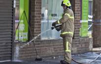 A fireman washes away bloodstains after a security guard was shot dead with another man fighting for his life after a drive-by shooting outside a popular Melbourne nightclub on 14 April 2019. Picture: AFP