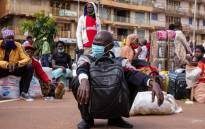FILE: A traveller wears a face mask, as a preventive measure against the spread of the COVID-19 coronavirus, while he waits for an intercity bus at the Namirembe Bus Park in Kampala, Uganda, on 4 June 2020, the first day of re-opening public transport. Picture: AFP.