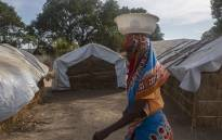 A woman walks through the huts at the 25 de Junio camp for the displaced people in Metuge on December 9, 2020 where over 16.000 displaced from the northern Cabo Delgado area are now sheltered. Picture: Alfredo Zuniga/AFP