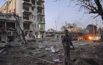 A man stands next to the Ambassador Hotel after al-Shabaab launched a deadly attack on the top Mogadishu hotel popular with MPs, setting off a car bomb and fighting security forces inside the complex on 1 June 2016. Picture: AFP.