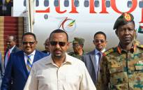 This file photo taken on 7 June 2019 shows Ethiopia's Prime Minister Abiy Ahmed (C-L) walks alongside Shams-Eddin Kabashi Sudan's Transitional Military Council (TMC) spokesman (C-R) upon his arrival at Khartoum international airport on 7 June 2019. Picture: AFP