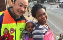 Johannesburg MMC for Public Safety Michael Sun hands out a rose to a woman as part of his department's celebration of Women's Month. Picture: @MichaelSun168/Twitter.