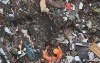 A rescue worker along with a sniffer dog searches for survivors in the rubble of a collapsed five-storey apartment building in Mahad on 25 August 2020. Picture:  AFP