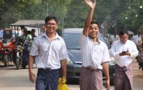 Reuters journalists Kyaw Soe Oo (C) waves beside colleague Wa Lone (L) as they walk out of Insein prison after being freed in a presidential amnesty in Yangon on 7 May 2019. Picture: AFP.