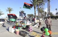 A vendor stands next to products he is selling, including the national flag, ahead of the eighth anniversary of the Libyan revolution which toppled late leader and strongman Moamer Kadhafi, in the capital Tripoli on 9 February 2019.  Picture: AFP